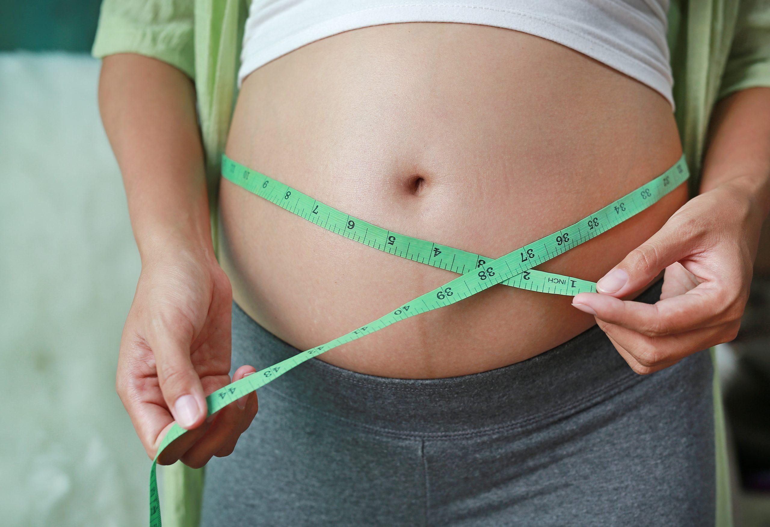 kobieta mierzy brzuch
